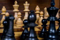 Close up white and black chess figurines on a chess board. With wooden background Stock Photos