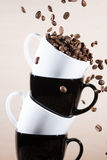 Close up of white and black cups on the stack with falling down brown roasted coffee beans. Stock Image