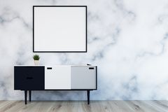 White, gray and black chest of drawers, marble. Close up of a white, black and gray chest of drawers and a vertical poster hanging in a marble wall living room Royalty Free Stock Image