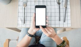 Close up white blank screen mobile over restaurant table order food online.  royalty free stock photo