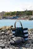 Close up of a white and blue bag and fashion coats on the beach of Genoa, Italy Stock Photo