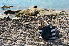 Close up of a white and blue bag and fashion coats on the shore of the sea Royalty Free Stock Photography