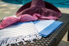 Close-up of white, blue and beige Turkish peshtemal / towel, pink bikini top and straw hat on rattan lounger. Royalty Free Stock Image