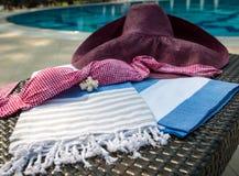 Close-up of white, blue and beige Turkish peshtemal / towel, pink bikini top, straw hat and white seashells on rattan lounger. Stock Photography