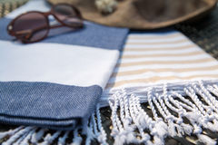 Close-up of white, blue and beige Turkish towel, sunglasses and straw hat on rattan lounger. Concept of summer accessories close-up of white, blue and beige Stock Image