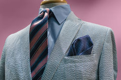 White & Blue Seersucker Jacket With Striped Tie. Close-up of a white & blue seersucker jacket with blue shirt, pink & blue striped tie on a pink background Royalty Free Stock Images