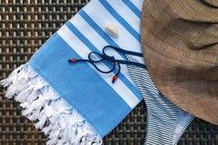 Close-up of a white and blue Turkish peshtemal / towel, bikini, white seashells and straw hat on a rattan lounger. Stock Photos