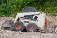 A close up of a white bobcat s550 or skid loader on construction site. stock photography