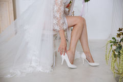 Close-up of white bridal shoes fixing on her legs Royalty Free Stock Photography