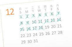 Close up of a white calendar page on December. Close up of a white calendar page with some of the days crossed off with a green X royalty free stock image