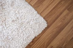 Close-up white carpet on laminate wood floor in living room, interior decoration. Close-up white carpet on laminate wood floor in living room , interior royalty free stock photos