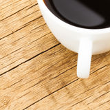 Close up of white ceramic coffee cup on old wooden table - view from top. Close up of white ceramic coffee cup on old wooden table Stock Photography