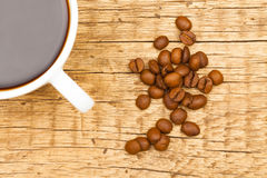 Close up of white ceramic coffee cup with roasted coffee beans on wooden table - view from top Royalty Free Stock Image