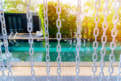 Close-up The white chain curtain and blur swimming pool Royalty Free Stock Image