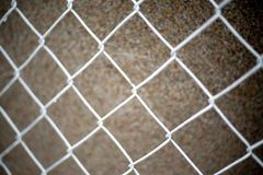 Close up white chain link fence on brown dark background.  royalty free stock images