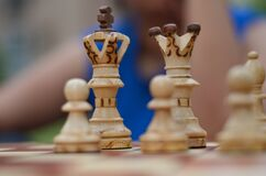 Close up of white chess pieces with focus on queen and king and pawn blurred out in background and foreground. Concept - idea,