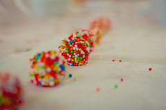 Close up on white chocolate balls covered with candies arranged in a row. Narrow focus royalty free stock images