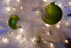 Close up of white Christmas tree with green ornaments. Close up of artificial white Christmas tree branches with metallic green ornaments and white lights royalty free stock images