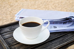 Close up white coffee cup on wood table at sunrise sand beach with newspaper in the morning Stock Photos