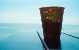 Close up white coffee cup on wood table and view of sunset or sunrise background Stock Images