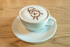 Close up a white cup of coffee with cartoon latte art made from cocoa powder. On wooden table background royalty free stock images
