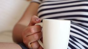 Close-up of a white Cup of coffee in the hands of a girl who lies on the bed. Close-up of a white Cup of coffee or tea in the hands of a young girl who lies on stock video