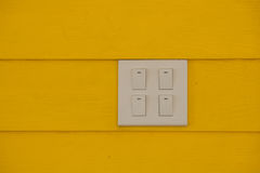 Close up white electricity switch or light switch on yellow color wall background. stock images