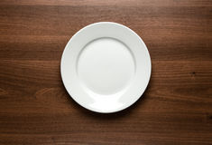 Empty plate at the table. Close up of white empty plate at the wooden table with copy space Royalty Free Stock Photo