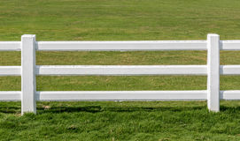 Close up white fences with green field background. Royalty Free Stock Photo