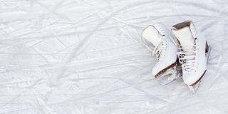 Close up of figure skates and copy space over ice background with marks from skating or hockey. Close up of white figure skates and copy space over ice royalty free stock image