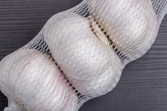 Close up white garlic bulbs in net packaging, general and useful Royalty Free Stock Photography