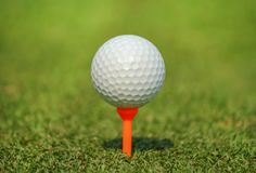 Close up white golf ball on orange tee at green grass. In golf course Stock Photo