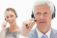 Close-up of a white hair man with a woman talking in background. Close-up of a white hair men with a women talking in background while wearing a headset against Royalty Free Stock Image