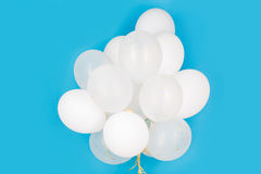 Close up of white helium balloons over blue Stock Photo