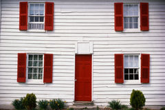 Close up of a white house with red shutters. Royalty Free Stock Photos