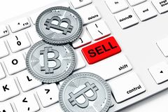 Sell, cryptocurrency and sales concept. Close up of white keyboard with red button and silver bitcoins. Sell, cryptocurrency and sales concept. 3D Rendering Stock Image