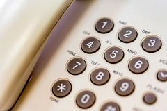 Office telephone keypad close. Close up white landline phone with grey buttons Royalty Free Stock Images