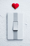 Close up of white light switch with a red heart Royalty Free Stock Photos