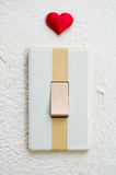 Close up of white light switch with a red heart Royalty Free Stock Image