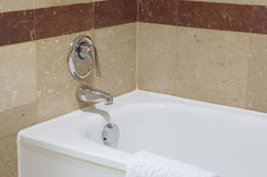 Close up white luxury bathtub with chrome faucet. On brown tile wall Stock Photo