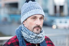 Close up of white male in city. Portrait of white guy on street. Bearded man in winter hat with ball and red jacket. Close up of white male in city. Portrait of Royalty Free Stock Photography