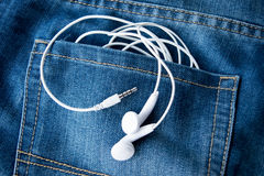 Close up white Mobile Headsets in jeans bag Royalty Free Stock Images