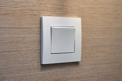 Interior white modern light switch. Close up white modern light switch with wooden texture background. Copy space Royalty Free Stock Images