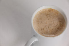 Close-up of white mug of coffee with creamy froth Stock Images