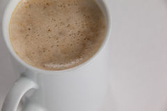 Close-up of white mug of coffee with creamy froth Royalty Free Stock Image
