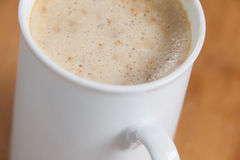 Close-up of white mug of coffee with creamy froth Stock Image