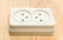 Close-up of a white outlet on a wooden table stock photos