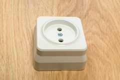 Close-up of a white outlet on a wooden table. stock photos