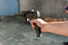 Close up of white persona arm with hand holding black toy gun outdoors during sunny day stock images