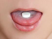 Close-up of a white pill in the male's mouth. Round tablet on th royalty free stock photos